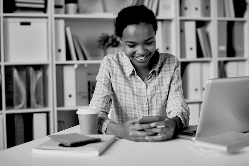 Portrait of smiling African girl using smartphone in school library browsing social media and studying